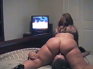 She sits on his face and watchs TV