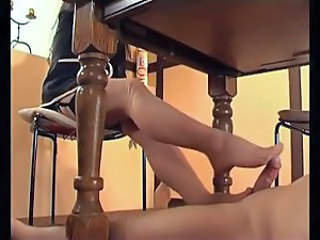 He lies under table and gets a stockings footjob