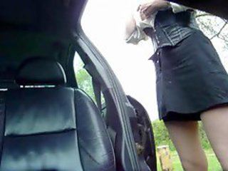 Milf in a slutty contraption sucking cock in car seat