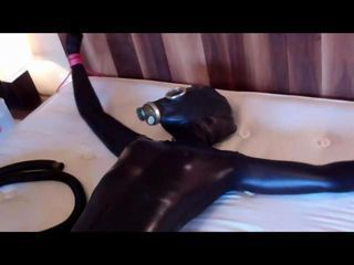 Adreena visits and surprises us as she is wearing a black shiny zentai catsuit Her total enclosure is completed by rubber gloves and crotch high rubber boots Over her hood we add a rubber gas mask and you first see her tied to the bed at wrists