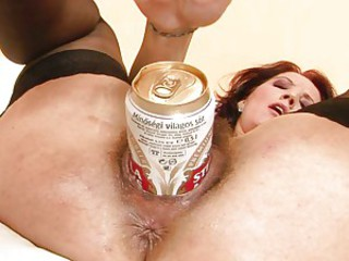 A slutty babe uses a can of beer to fill her hungry hot cunt