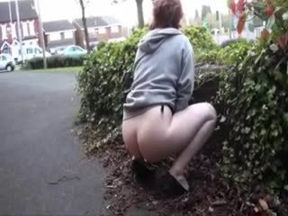 Redhead pees in the bushes in public
