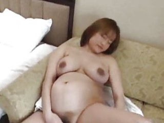 Very pregnant Asian is using a toy