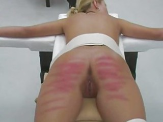 Teen women are strapped to a panel and caned