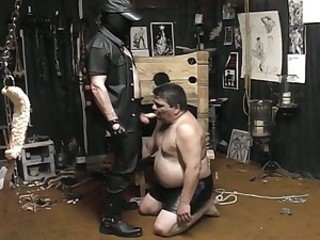 Masked guy unbinds his fat slave and makes him blow his cock