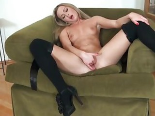 This tender blonde in black stockings can't keep her playful fingers off her shaved pussy. Sweet chick Amanda Blake has a good time fingering her neat shaved pussy in a big armchair.
