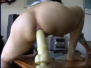 Masked girl rides a toy with her ass