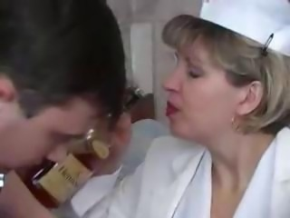 Naughty blonde granny nurse takes a nip from the bottle added to his boner