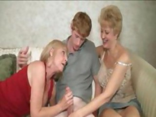 Two mommies sucking a teen cock