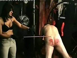 Mistress with beautiful big tits hits slave on the ass with a stick till its...