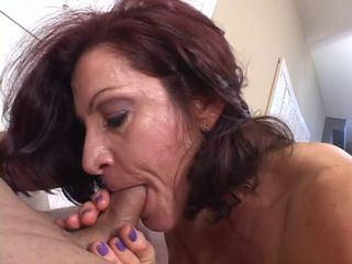 Hot mature brunette masterfully sucks cock while smoking a cigarette