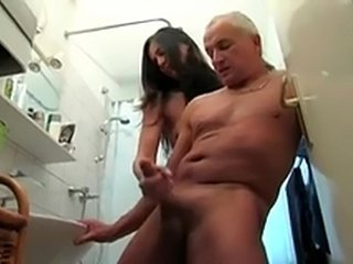 Old dude gets jerked off in the bathroom by a young gal