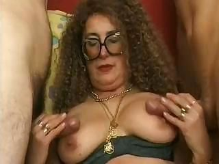 Middle-aged slut jerks two tasty dicks and takes them in her holes