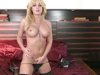 Blonde Haired Bombshell Angela Sommers In Black Stockings Takes Off Her Tiny Thong Panties Before She Sticks Her Fingers In Her Love Tunnel. Watch Her Masturbate On Her Red Bed.