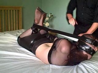 Karina is mummified in pantyhose and hogtied with her feet tied to her thighs using the spare leg of the pantyhose