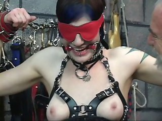 Gorgeous young blindfolded brunette in corset is tortured...