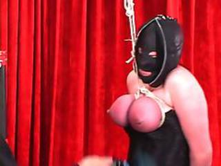 "Corseted shackled woman in leather hood gets tits bound so they become red"" class=""th-mov"