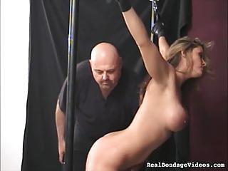 Busty Girl In A Bondage Device Takes A Light Flogging