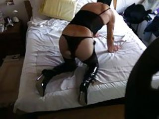 LADY F IN BED IN BLACK BOOTS AND STOCKINGS