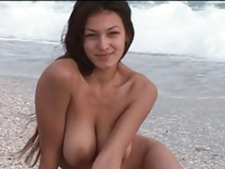 Brunette with big tits rolls around in the sand tubes