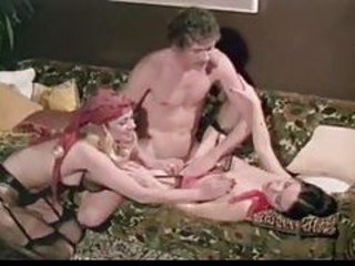 Classic threesome surrounding liberally hung John Holmes tubes