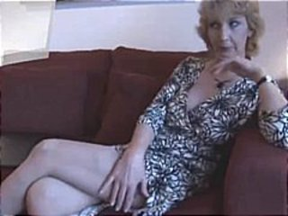 Blonde mature strips and shows off her pussy sitting on the couch