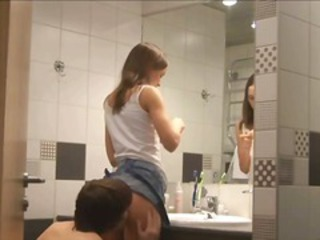 Young brunette girlfriend is getting ready in the bathroom and then gets licked up her skirt