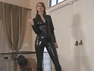 Redhead Kendra James is dressed in her black latex and posing