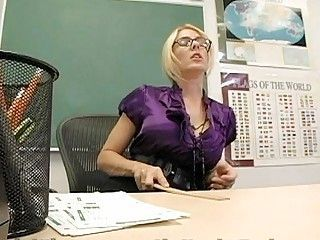 Blonde teacher with glasses strips in the classroom