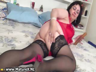 Horny busty housewife lays on the bed