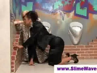 Video of two glamorous and fully clothed ladies sharing a fake cock at a gloryhole