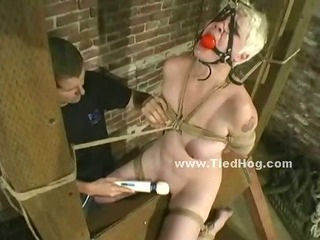 Brunette locked with chains on wooden table and with huge leish bound in ropes and and tortured