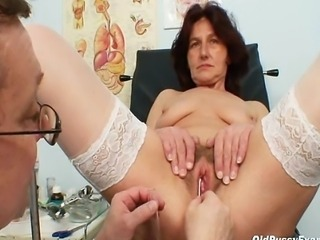 Pervy woman doctor examines hairy pussy grandma who is sitting on gyno chair...