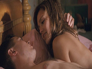 Jessica Alba lying on her stomach on a bed with her pants pulled down to...
