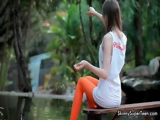 Petite brunette teen girl in sexy orange