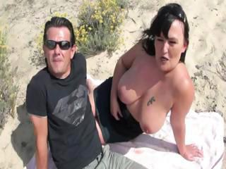 French busty brunette on the beach in a gangbang getting nailed