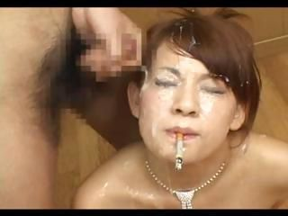 Japanese bukkake whore smokes while getting a cum shower