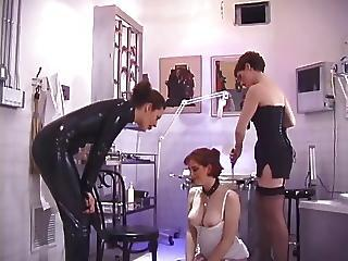 Brunette In Corset Garters And Stockings Lets Leather Mistress Paddle Her Ass