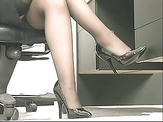 Young perky brunette coworker plays with a heavy toy at the office
