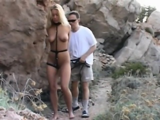 Promiscous blonde tied up by a stone and doggie drilled