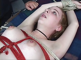 Pretty blonde is suspended with red and white ropes.