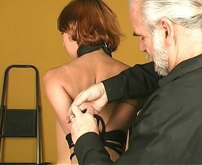 Coxcomb leads tall slim bdsm redhead in dog collar coupled with leash to shackle her