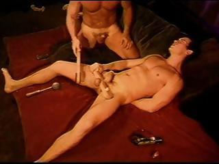 CBT hot young muscle stud s ball sack clamped off from his cock between two pieces of clamped wood.