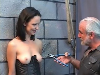 Gorgeous young inclusive in a bdsm corset is whipped and maltreated with pliers